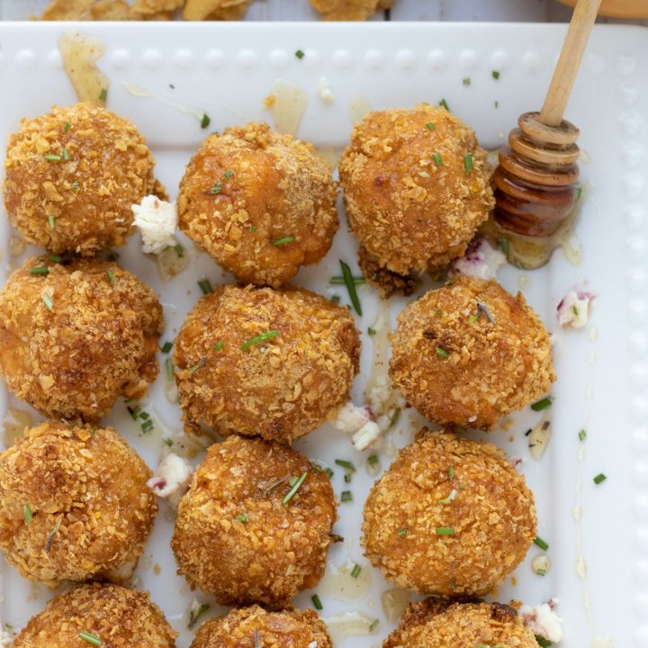 A square white dish with air fried goat cheese and sweet potato balls. They're drizzled with honey. you can see the honey stick with honey oozing off of it. The dish is sprinkled with fresh rosemary and there's corn flakes in the background