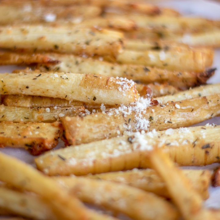 Parmesan rosemary baked parsnip fries on parchment paper