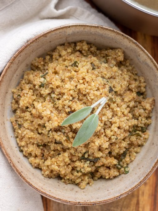 A brown bowl filled with toasted brown butter quinoa that's topped with two fresh sage leaves.  It's on top of a wooden surface with a beige cloth next to the bowl.