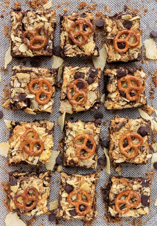brownie squares that are topped with a pretzel and crushed potato chips. There's crumbs sprinkled around the brownies with chocolate chips.