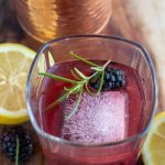 A square rocks glass with a large square ice cube, fresh rosemary sprig and a blackberry. It's filled with blackberry smash cocktail with fresh lemons and a copper cocktail shaker in the background.