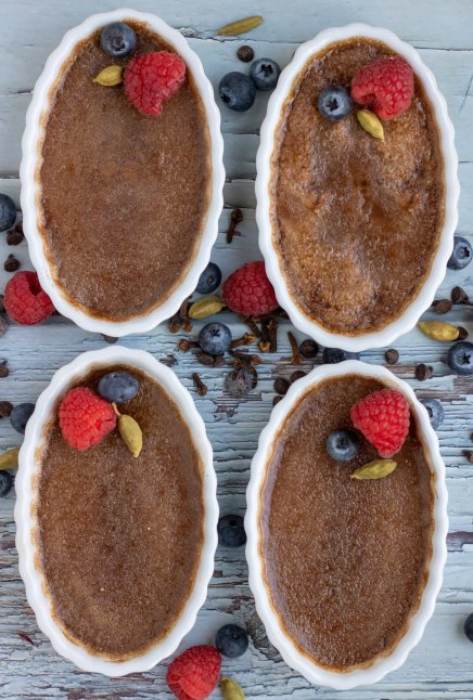 4 white oval ramekins with chocolate creme brulee. They're each topped with a fresh raspberry, blueberry and cardamom pod.