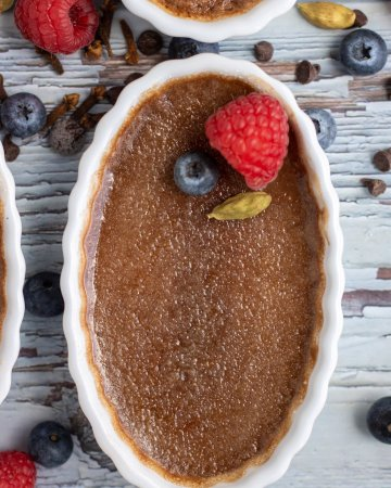 A white oval ramekin filled with chocolate chai creme brulee that's topped with fresh berries. There's fresh blueberries, raspberries, whole cardamom pods and chocoalte chips in the background.