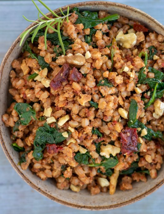 A brown speckled bowl filled with farro, sun dried tomatoes, walnuts and spinach. There's a fresh rosemary sprig in the upper corner of the bowl