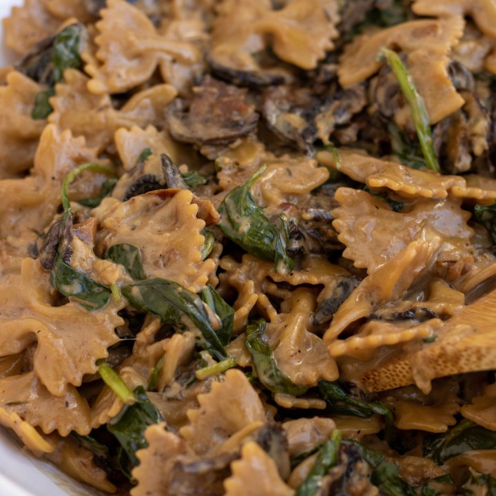 A large white bowl filled with farfalle pasta with spinach and mushrooms. It's tossed in a balsamic cream sauce.