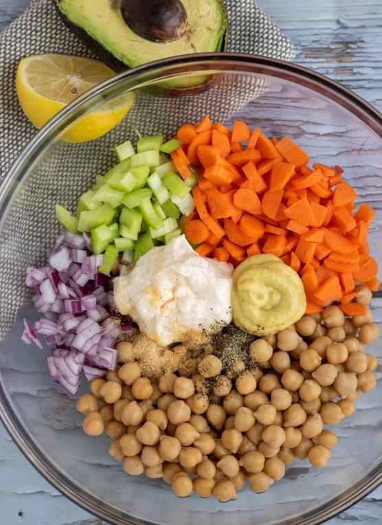 An overhead shot of a large clear bowl filled with chickpeas, diced carrots, diced red oninos, mayo, mustard, diced celery. There's a half of a lemon and avocado in the background