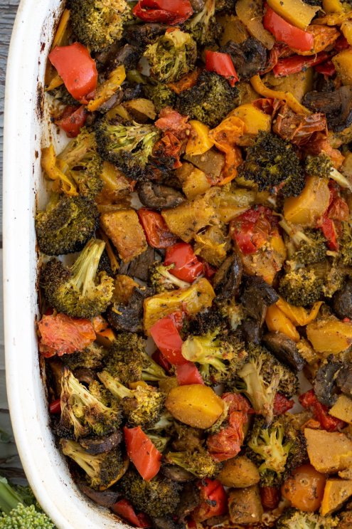 A rectangle white baking dish filled with roasted vegetables like broccoli, mushrooms and bell peppers