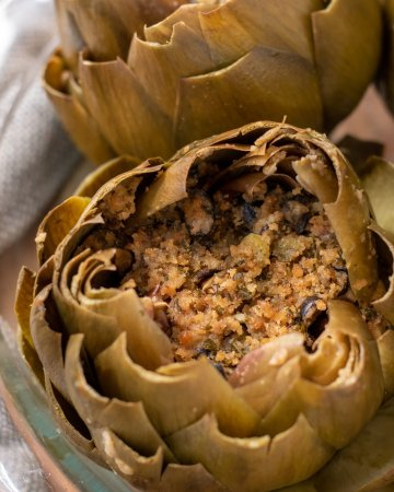 A glass baking dish filled with italian stuffed artichokes. They've been steamed and the leaves are opened up like flowers. They're stuffed with a breadcrumb stuffing.