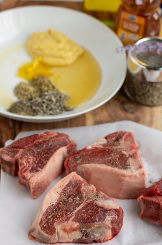 A wooden cutting board with raw lamb loin chops on it. There's a white bowl of the marinade ingredients and a jar of honey in the background.