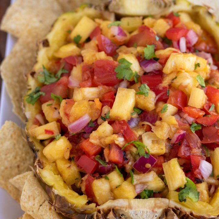 A half of a pineapple filled with fresh salsa and sprinkled with fresh cilantro. There's tortilla chips around the salsa and it's bright and vibrant