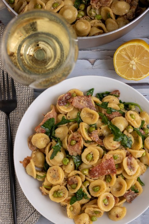 A white pasta bowl filled with creamy lemon pasta with peas, prosciutto and arugula. There's a glass of white wine next to the plate with a half a lemon and a large pot of pasta in the background