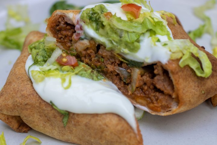 A crispy healthy air fryer beef chimichanga that's cut in half so you can see the ground beef and refried bean filling. It's topped with sour cream, guacamole and shredded lettuce