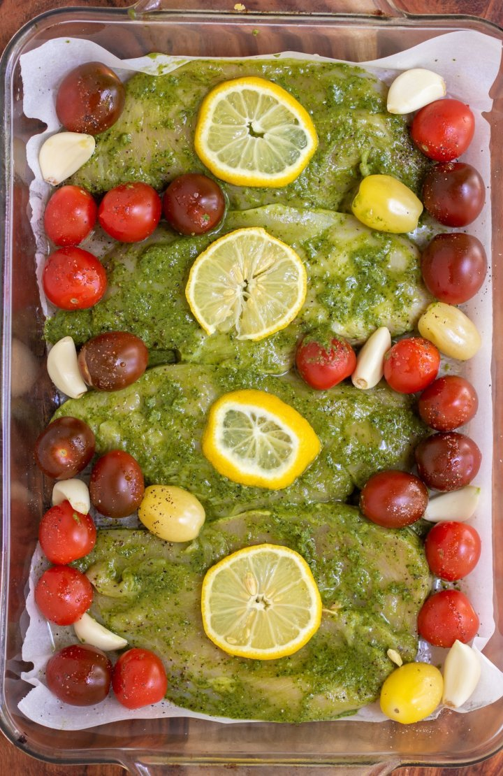 A rectangle glass baking dish lined with parchment with mixed cherry tomaotes, garlic cloves, and pesto marinated chicken breasts that are topped with a lemon slice