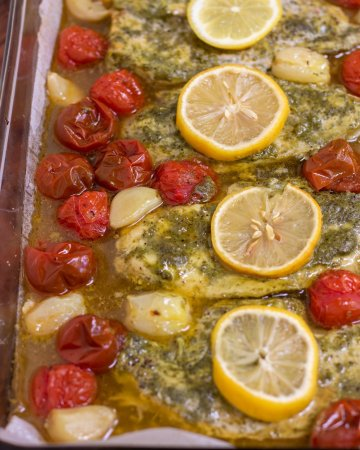 A glass baking dish with four pieces of chicken breasts that are covered in basil pesto and topped with a slice of lemon. There's roasted whole cherry tomatoes and garlic cloves around the chicken.