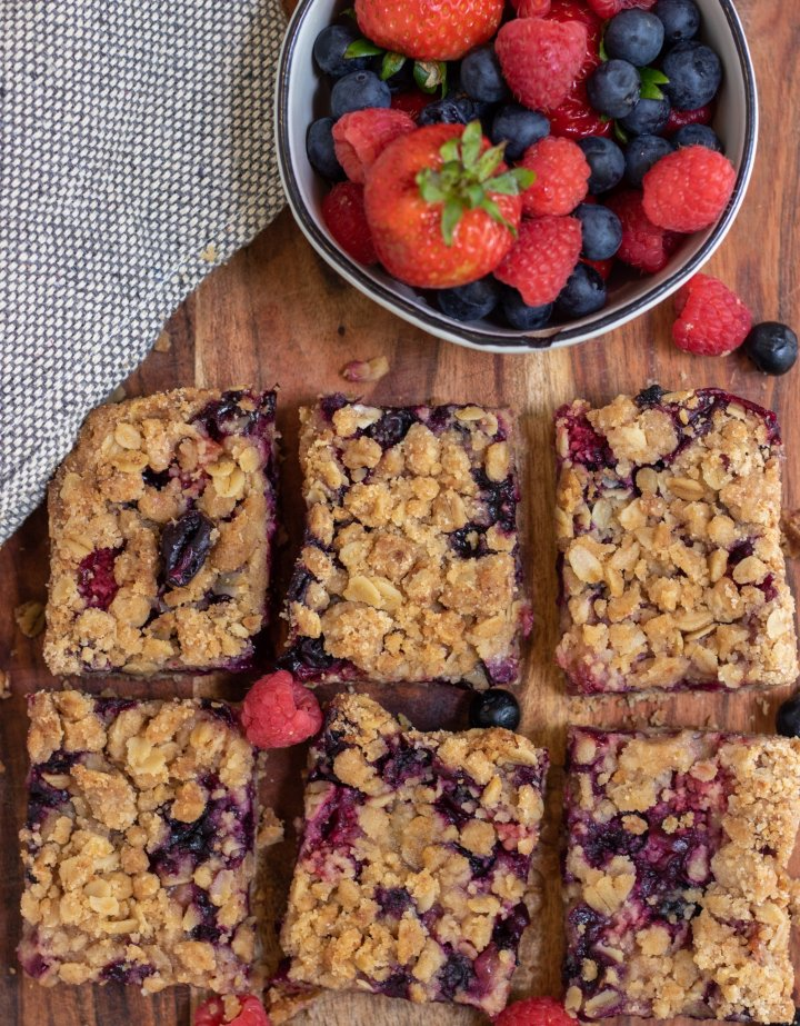 6 square berry crumble bars with a small bowl of fresh mixed berries next to them.