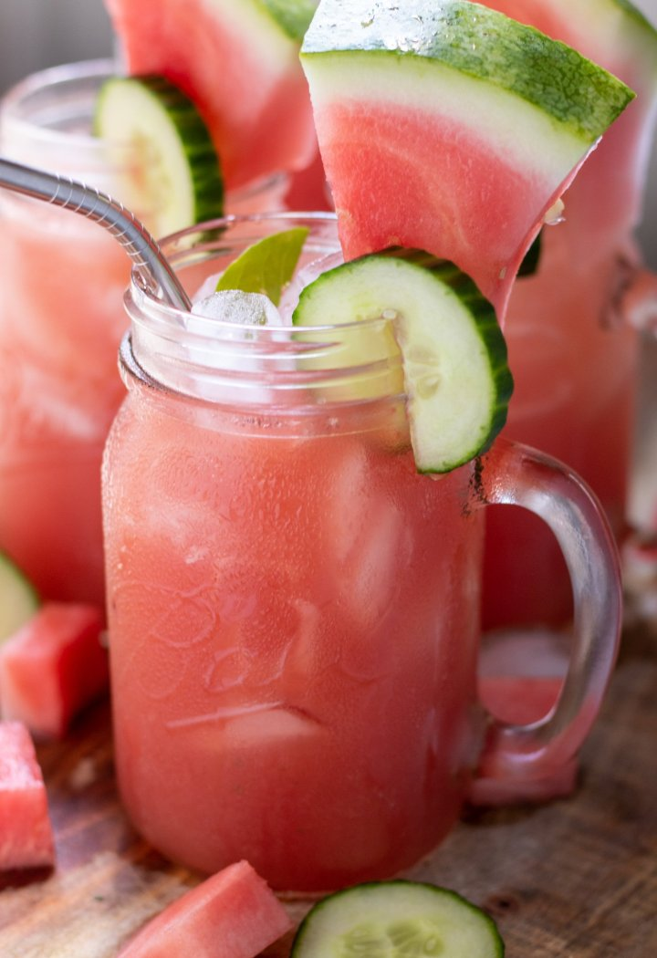 mason jar drink glasses filled with watermelon lemonade. They're garnished with a cucumber slice and small lemon wedge on the rim. The glasses have a metal drinking straw in them with ice in the glass.