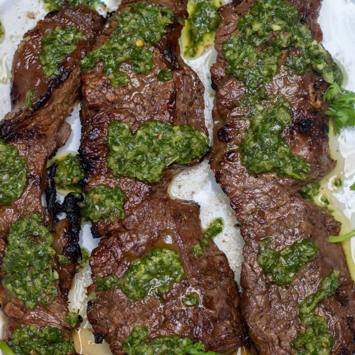 A white round dish topped with 3 grilled sirloin steaks that are drizzled with chimichurri sauce. There's fresh cilantro and a wedge of lime on the plate.