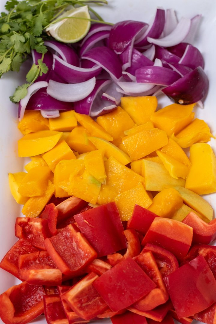 A large white serving platter filled with chunks of red bell pepper, mangoes, and red onions. There's a half of a lime and a bunch of fresh cilantro off to the side