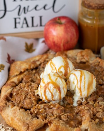 Apple crostata topped with 3 scoops of vanilla ice cream that's drizzled with caramel sauce. The crostata has an oat crumble and it's golden brown. There's a napkin with fall leaves next to it and a red apple with a jar of caramel sauce in the background