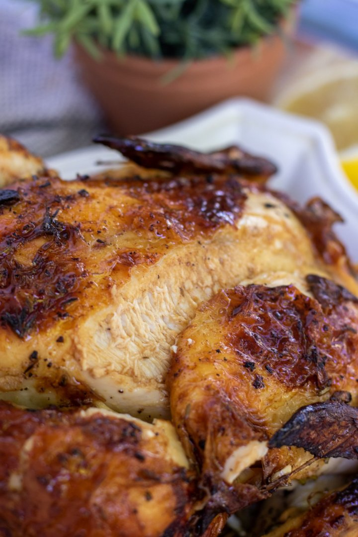 A roast chicken that's been sliced along the breast. The meat is white and juicy and the skin is golden and crispy. There's fresh rosemary and half of a lemon in the background