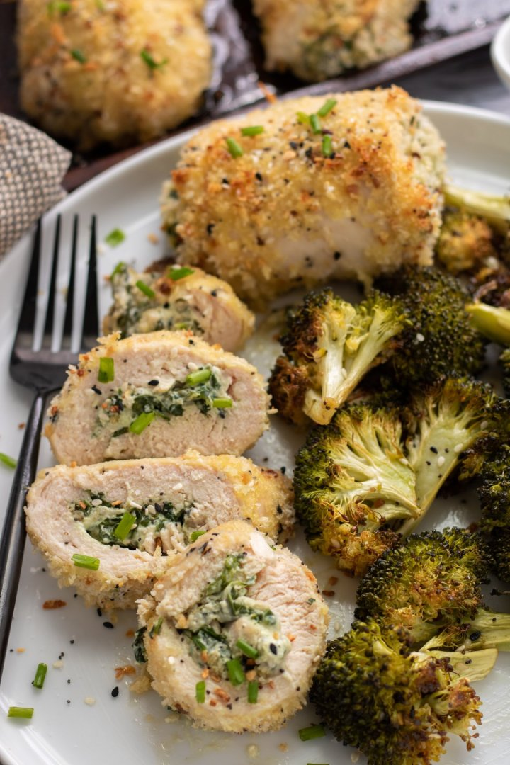 A white dish with sliced stuffed chicken that's been rolled up with cream cheese and spinach. There's roasted broccoli next to the plate with a whole baked chicken breast in the background. The chicken is coated in panko and it's golden. There's a black fork next to the chicken on the plate