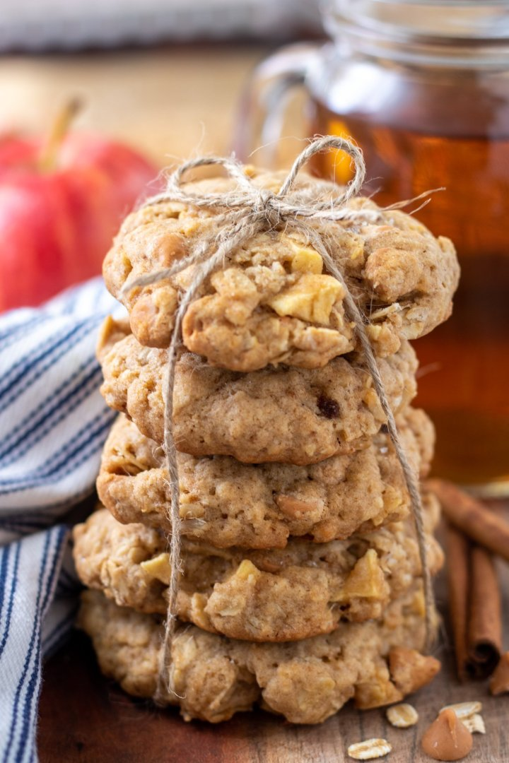 A stack of oatmeal cookies tied together with string. There's two cinnamon sticks next to it and a glass of hot apple cider in the background with a red apple
