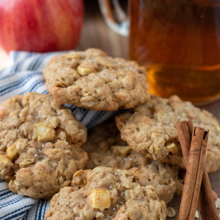 5 apple oatmeal cookies on a wooden surface. There's two cinnamon sticks next to the cookies. A red apple and a mason jar glass of hot apple cider are in the background
