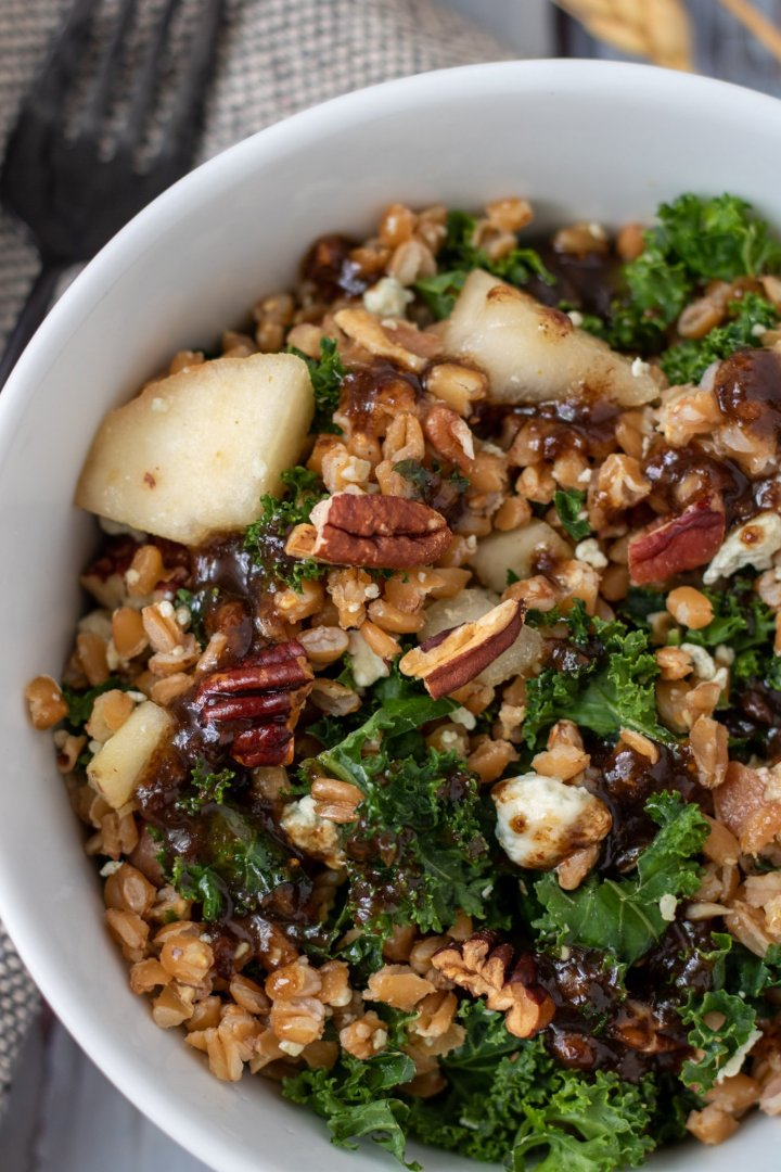 A white bowl filled with farro and kale salad with pecans, bacon, pears and Gorgonzola. There's a black fork next to the bowl.
