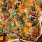 A glass baking dish with enchilada casserole. It's topped with fresh cilantro. You can see the colorful veggies in the casserole