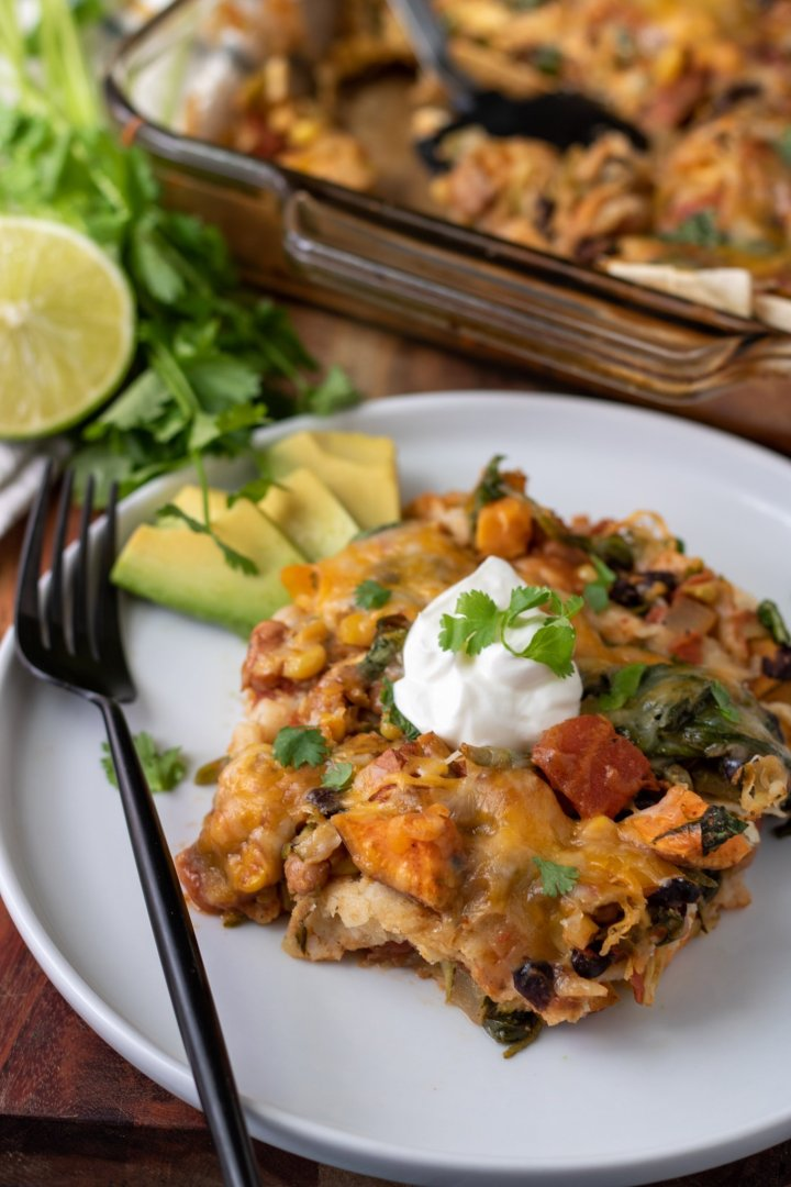 A white round dish with a piece of vegetarian enchilada casserole. It's topped with a spoonful of sour cream and sprinkled with fresh cilantro. There's sliced avocado on the plate and a black fork. There's half of a lime and a bunch of fresh cilantro in the background