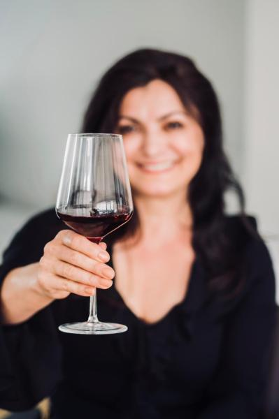 Senay Ozdemir smiling and holding a glass of wine