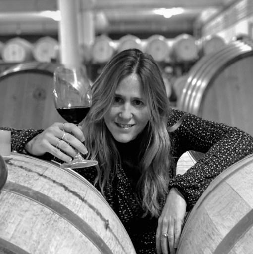 Clara Herrero holding a glass of wine in-between barrels