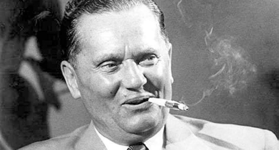 Marshal Broz Tito smiling and smoking cigar.