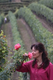 Chiara enjoying the sweet summer fragrance of roses in the vineyards.