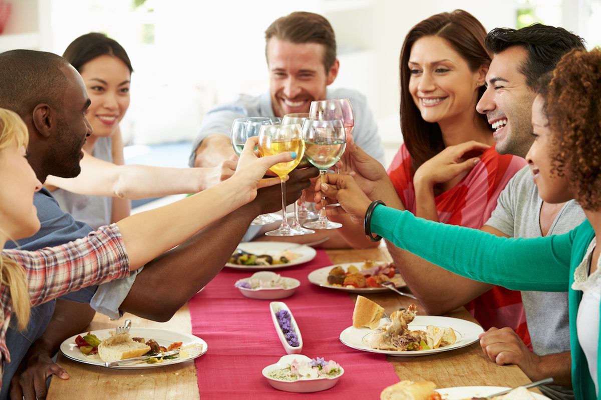 Group Of Friends Making Toast Around Table At Dinner Party drinking wine