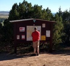 "Jason standarding at the ""exit"" of our off-roading adventure. The map and trailhead were positioned ""behind"" some trees when you drove in, we missed the map. Although on the map the road we traveled it was marked like any other major road."