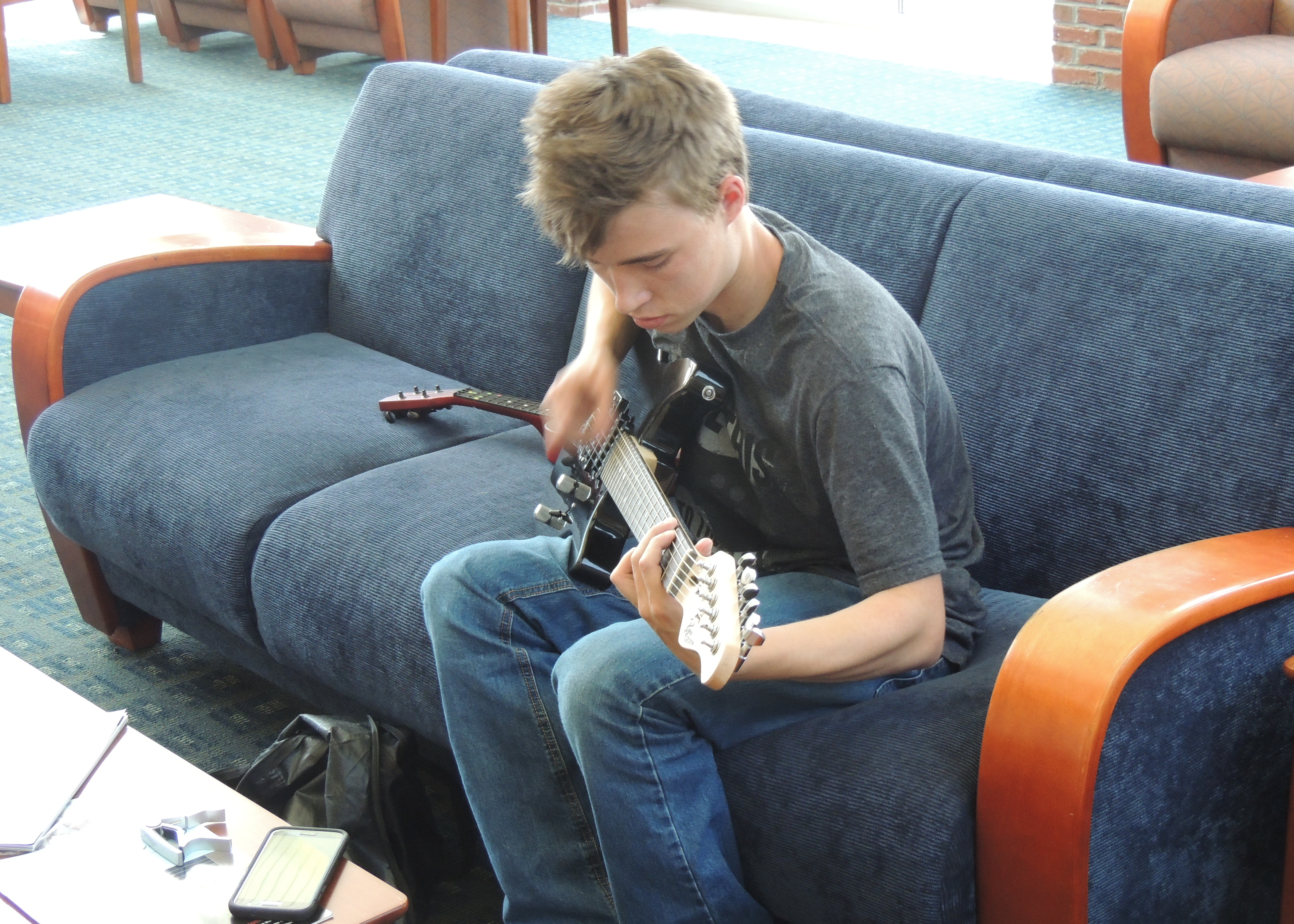 Matthew with his guitar while waiting for his Dad.... (He is very GOOD)