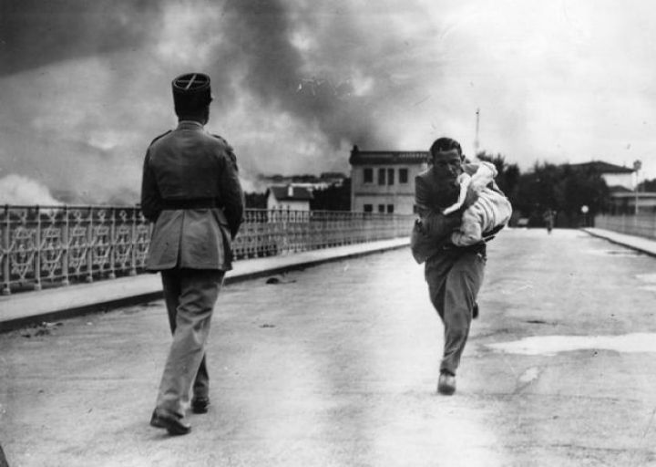 29 Powerful Pictures - During a civil war in 1936, a journalist dashes across a bridge to rescue a baby.
