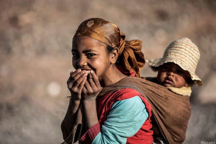 29 Powerful Pictures - A young girl carrying her baby in Marocco.