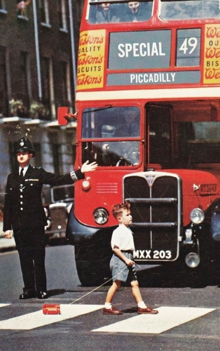 29 Powerful Pictures - A boy pulling his toy double-decker across a London street in the 1960's.