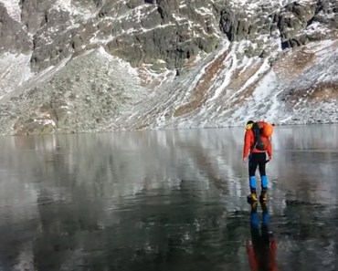 Hikers Walking on Crystal Clear Ice in the High Tatras Mountains.
