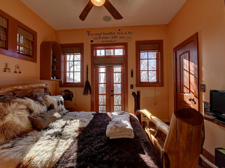 """The main bedroom features a king-sized bed with a heartwarming message above the door, """"The most beautiful view is the one I share with you""""."""