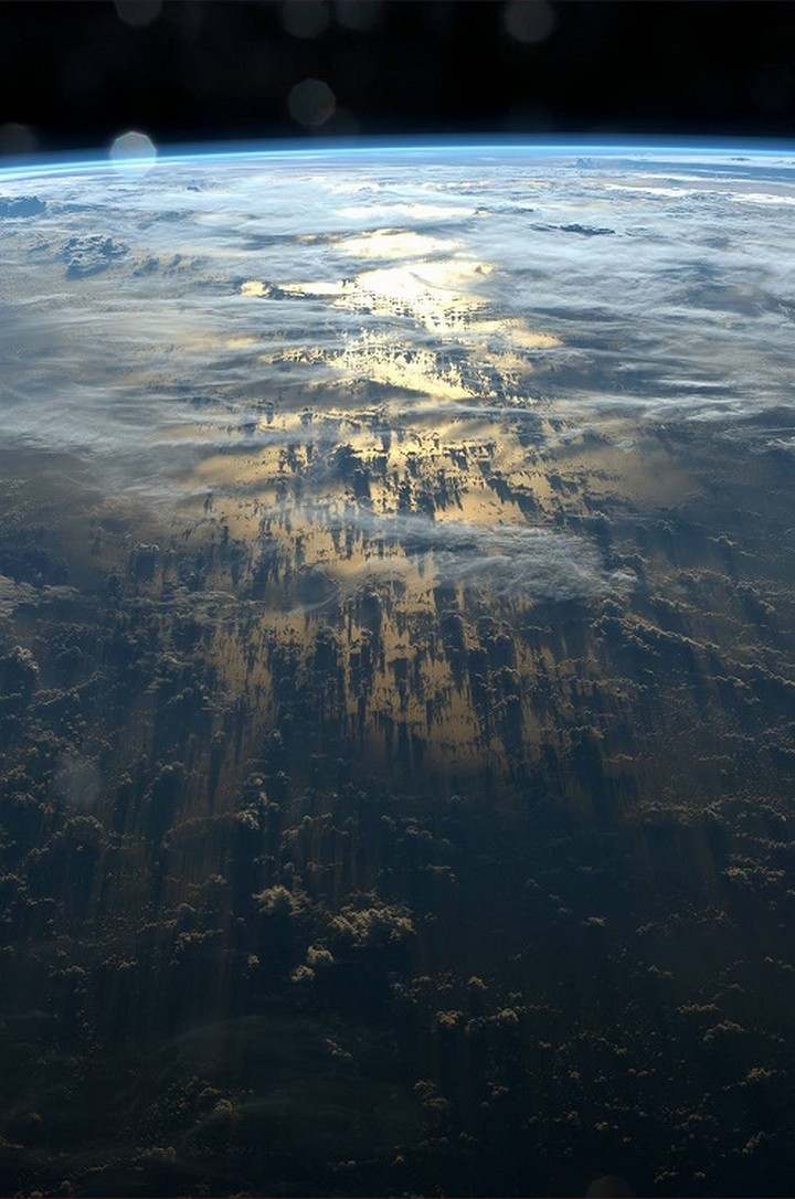 21 Awe-Inspiring Photos - Clouds casting shadows on earth as seen from the International Space Station.