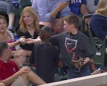 A Young Boy Gives His Baseball to a Pretty Woman Behind Him.