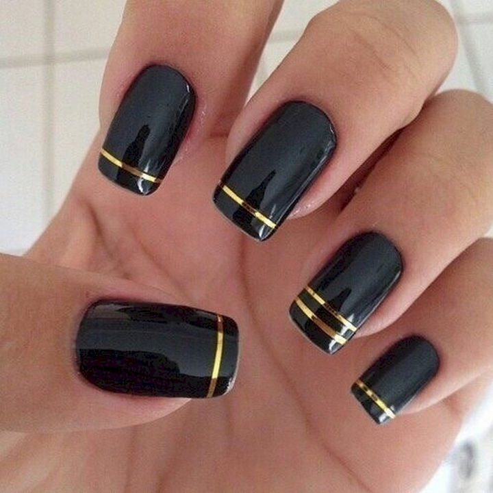 22 Black Nails That Look Edgy and Chic - Elegant gold striped nails.