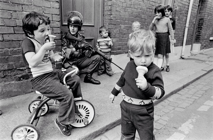 35 Rare Historical Photos - 1979: Children eat their ice cream cones while soldiers patrol the streets of Londonderry in Northern Ireland.