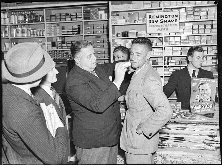 35 Rare Historical Photos - 1939: J.J. Hickey of Remington demonstrates the 'ease and comfort' of an electric shave on Ted Budrodeen, Mick Simmons tennis professional and coach, at a Mick Simmons store in Sydney.