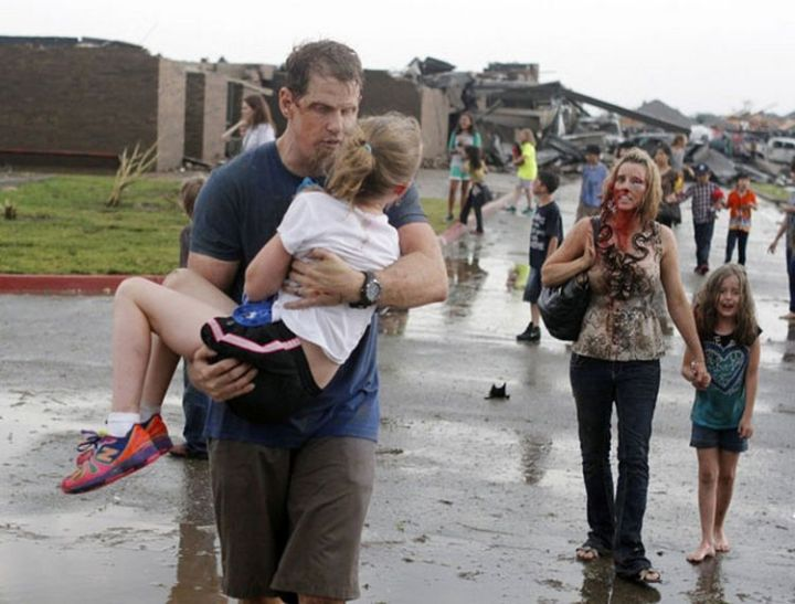 9 Heartbreaking Images - An injured family walks away from their destroyed neighborhood after a devastating tornado in Moore, Oklahoma.