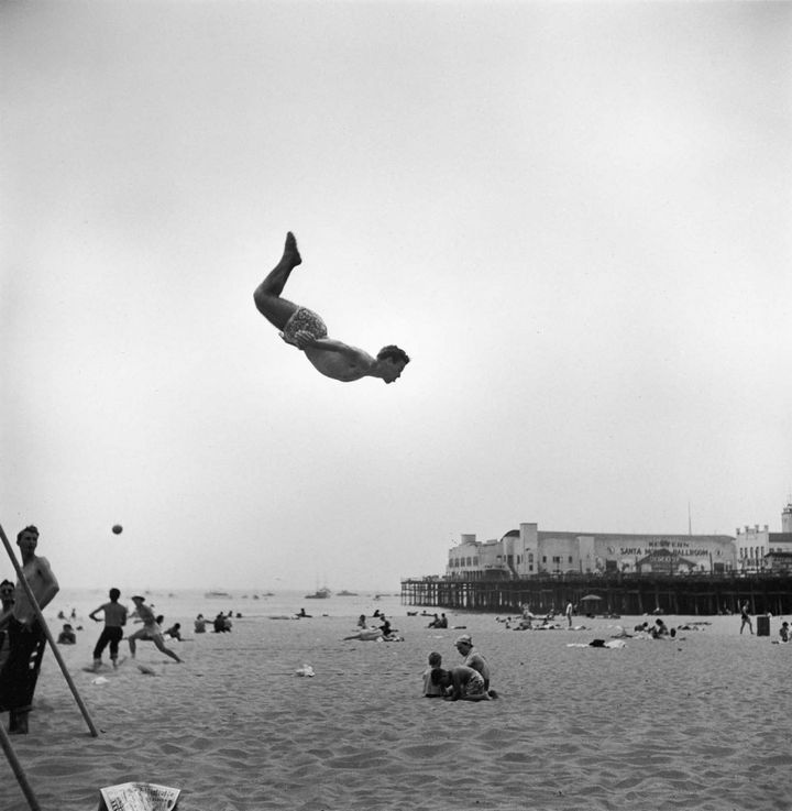 22 Timeless Images - A man jumps off a trampoline at a California beach.
