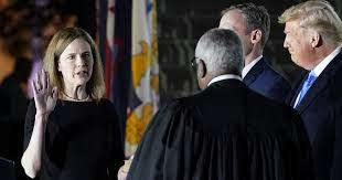 President Donald Trump applauds Amy Coney Barrett after she took her oath of office and was sworn in to serve on the court with just a week